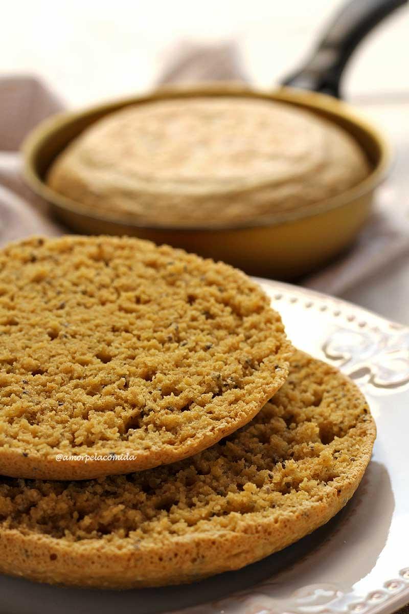 Pão redondo pequeno cortado ao meio mostrando a textura aerada da fatia sobre prato branco, ao fundo a frigideira com um pãozinho dentro desfocado da cena
