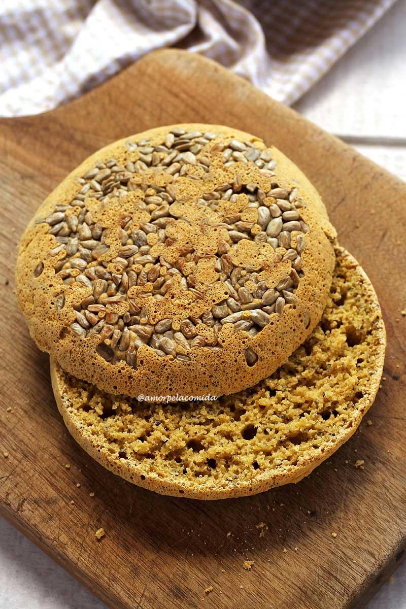 Pão de aveia de frigideira cortado ao meio, as duas fatias estão sobrepostas em uma tábua de madeira, na fatia de cima podemos observar as sementes de girassol decorando o pão