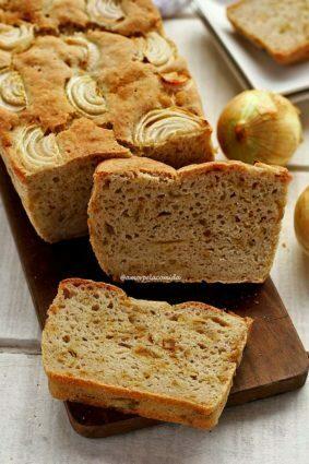 Pão de cebola sobre tábua de madeira retangular escura, sobre o pão fatias de cebola, o pão está fatiado com 1 fatia apoiada no pão cortado e a outra fatia deitada na tábua
