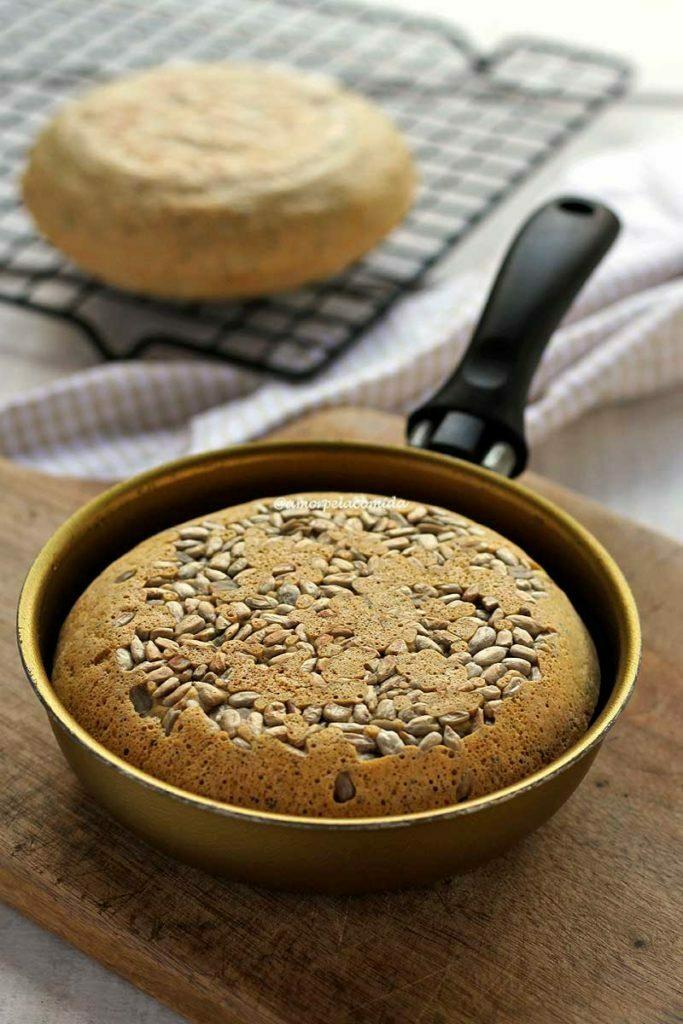 Pão pequeno dentro de uma frigideira dourada de 13 cm sobre uma tábua de madeira, ao fundo tem um pão de frigideira esfriando sobre uma grade preta