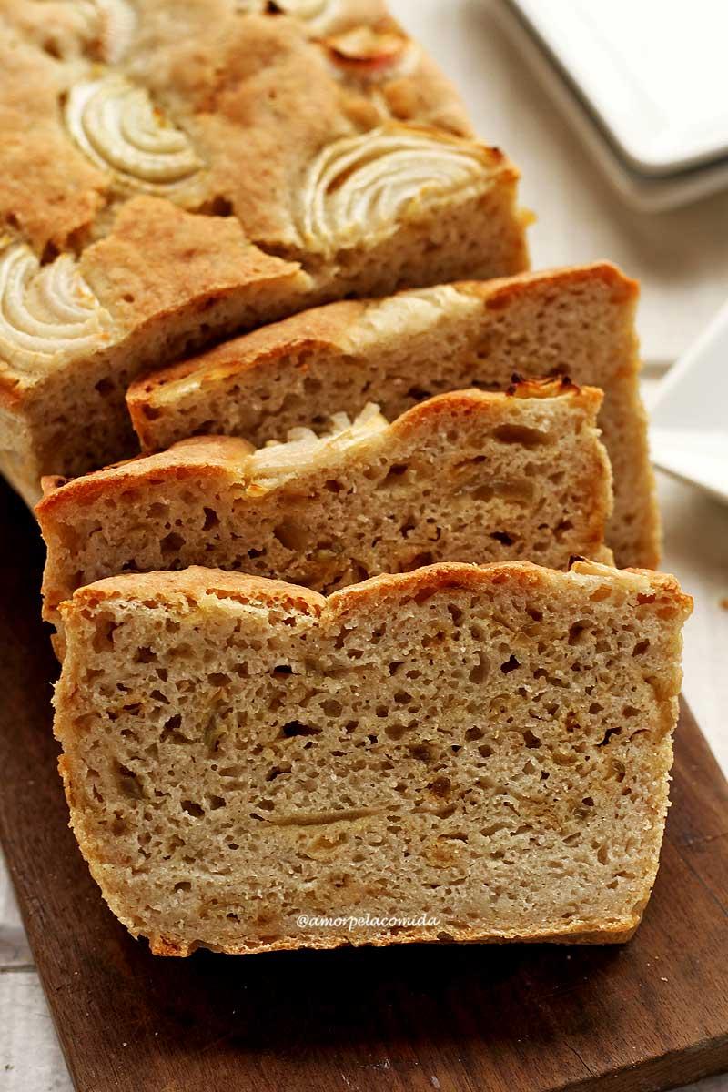 Três fatias de pão de cebola apoiadas no pão de cebola sobre uma tábua de madeira escura em uma mesa branca