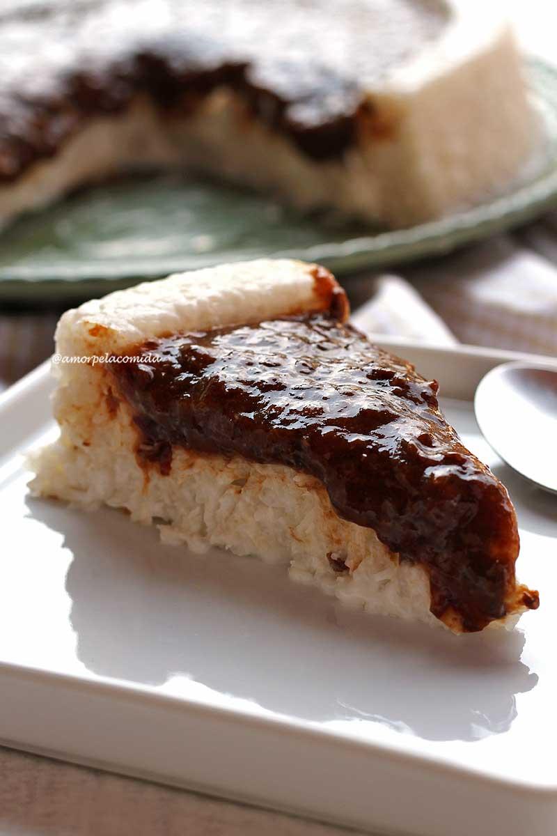 Fatia de bolo de tapioca com cobertura de ameixa preta sobre prato quadrado branco