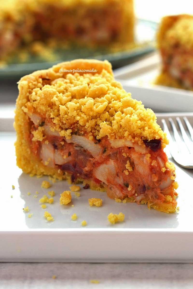 Fatia de empadão de palmito sobre prato quadrado branco, na foto aparece o recheio com bastante palmito, molho de tomate e azeitonas, na cobertura uma farofinha crocante