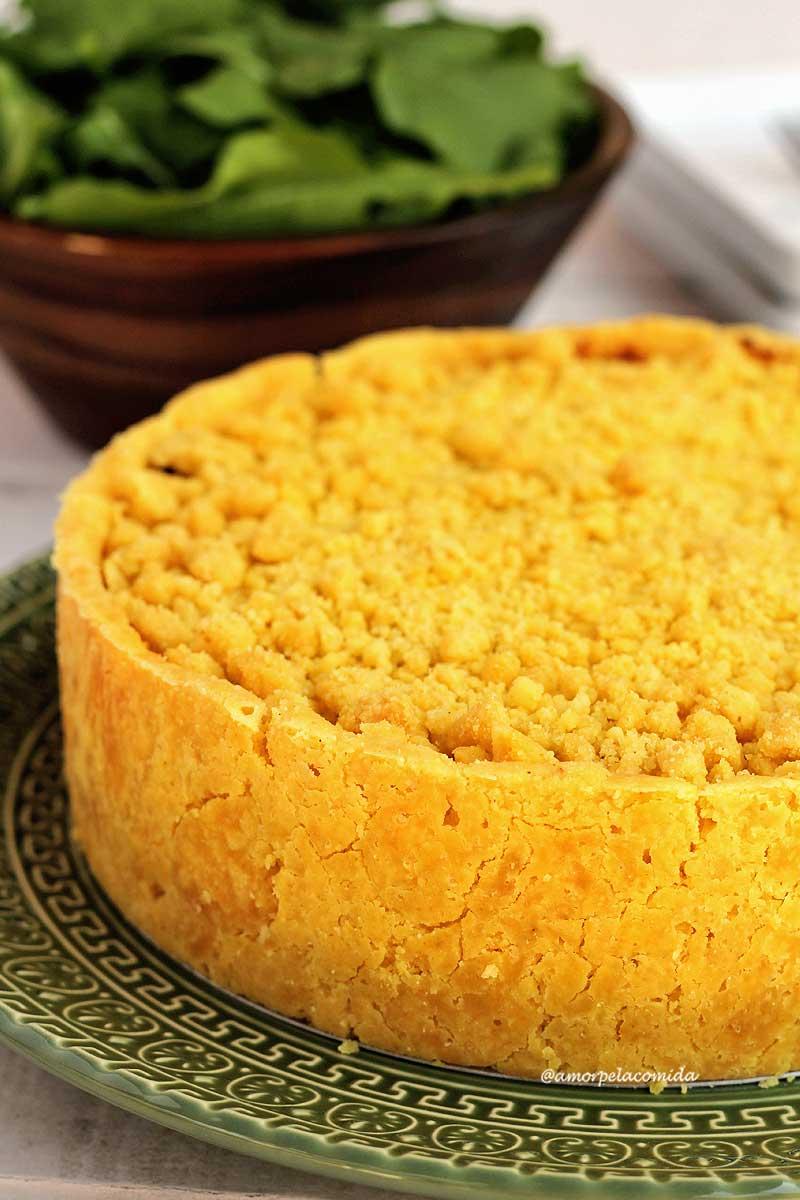 Empadão de palmito inteiro sobre um prato verde, a casquinha é crocante e a cobertura é uma farofinha feita com a mesma massa da crosta