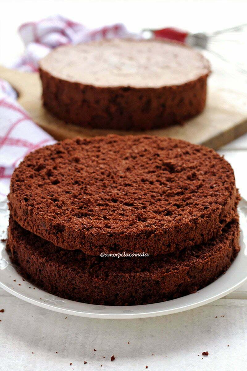 Pão de ló de chocolate cortado ao meio sobre prato branco, ao fundo outra massa de pão de ló sobre tábua de madeira
