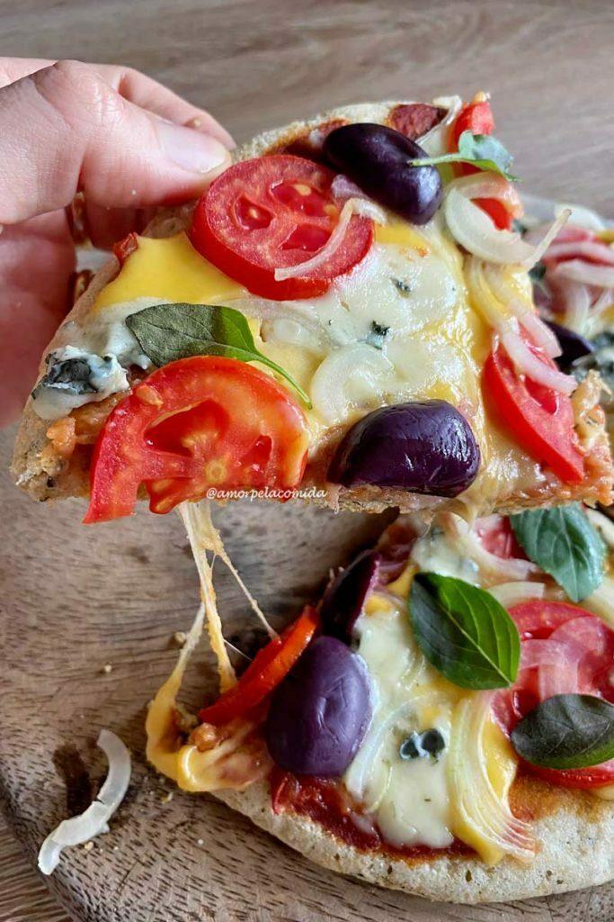 Mão segurando fatia de pizza, abaixo mais dois pedaços de pizza sobre uma tábua de madeira