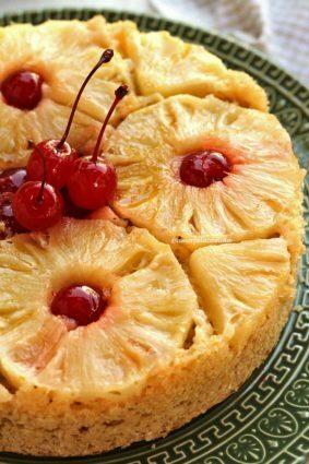 Bolo redondo com fatias de abacaxi decorando a superfície, no miolo do abacaxi tem cerejas e na parte central também, o bolo está sobre um prato verde