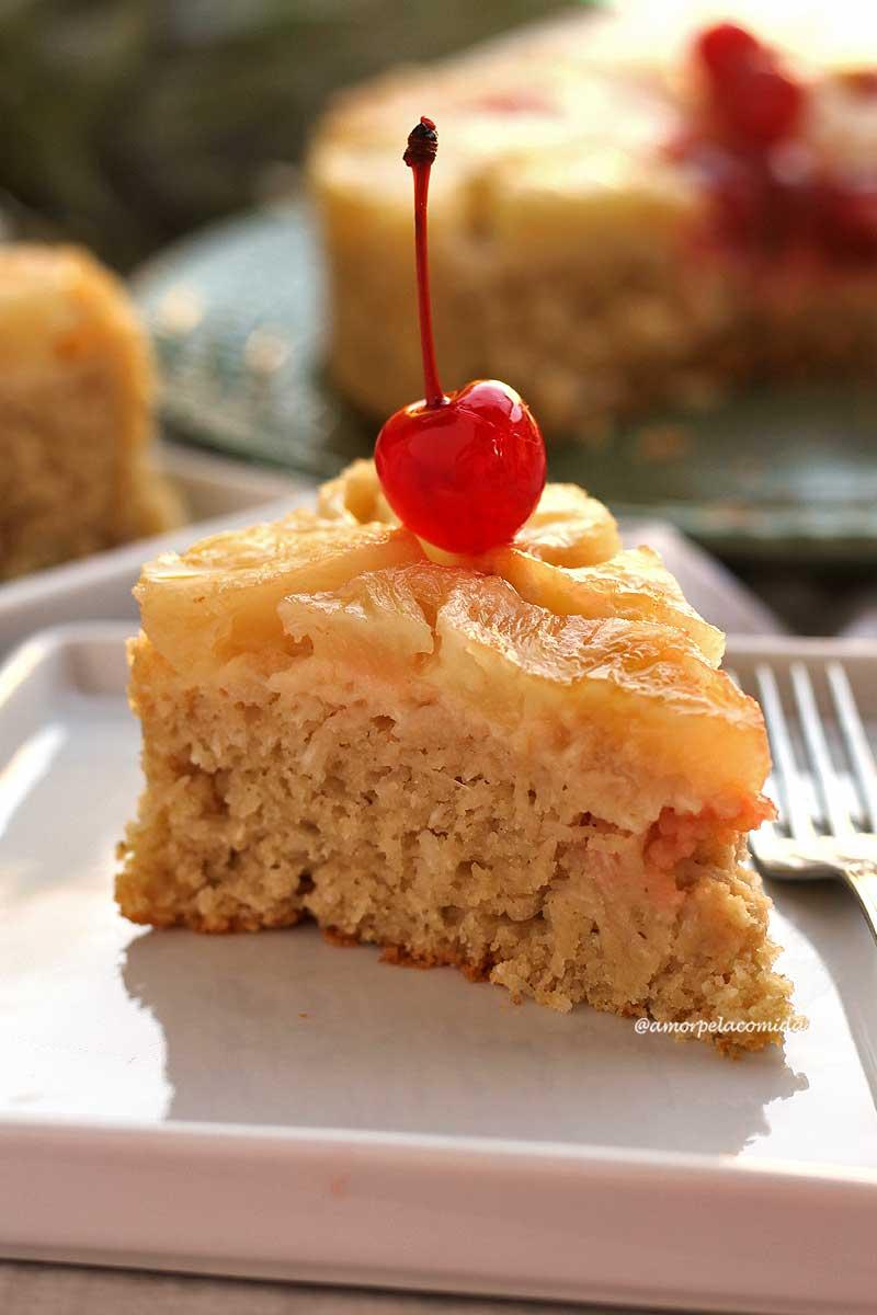 Fatia triangular de bolo de abacaxi com coco, no topo do bolo tem pedaços de abacaxi e uma cereja com cabinho