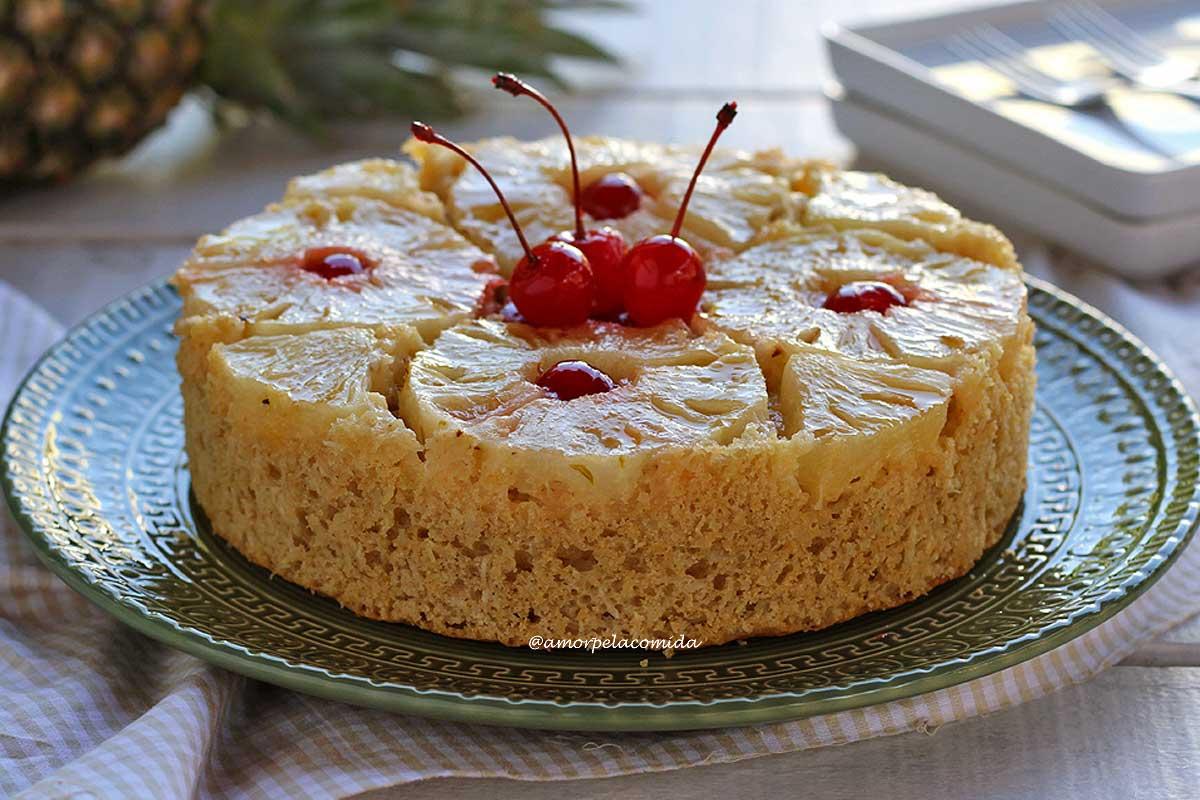 Bolo redondo sobre prato verde, no topo do bolo rodelas e pedaços de abacaxi e algumas cerejas enfeitando o bolo