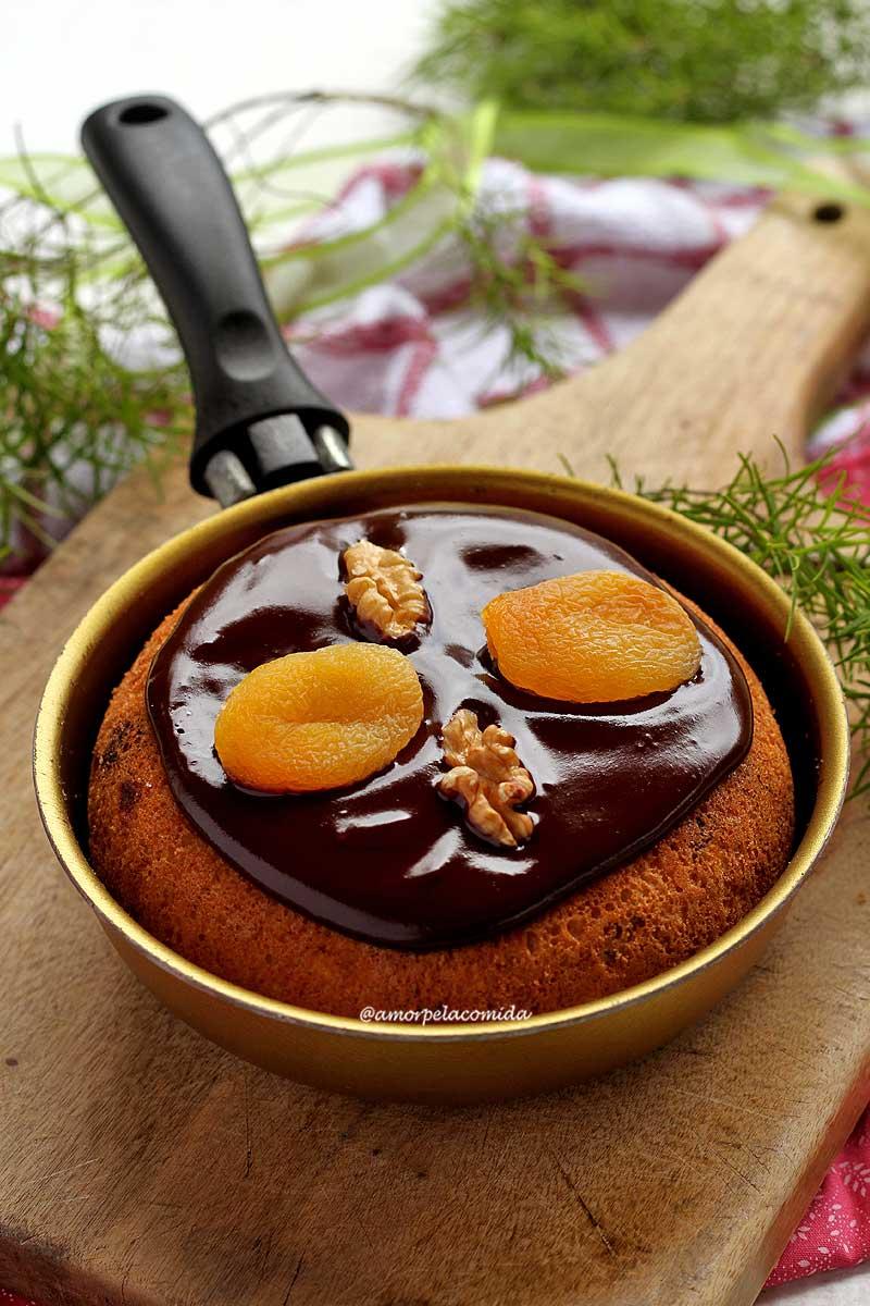 Frigideira pequena dourada sobre tábua de madeira, dentro um panetone decoraco com cobertura de chocolate cremosa com damasco e nozes