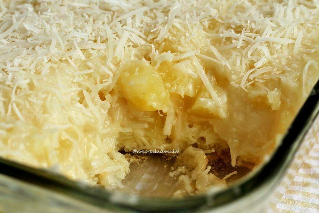 Travessa de vidro transparente com sobremesa de abacaxi, na base bolo e por cima um creme de abacaxi com coco e flocos de coco decorando