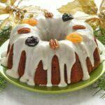 Bolo redondo com furo no meio decorado com calda branca, frutas secas e nozes em um prato verde