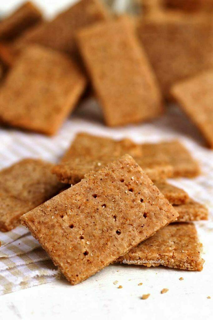 Biscoitinhos quadrangulares fininhos e crocantes com furinhos na superfície apoiados sobre um pano quadriculado bege e branco