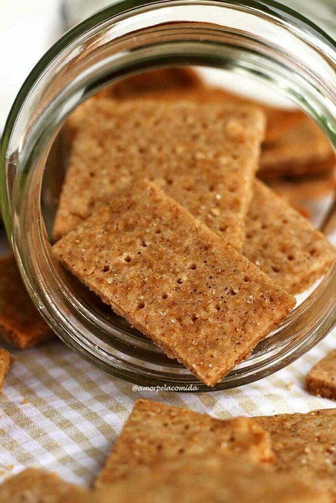 Biscoitinhos fininhos e crocantes de mel com canela saindo de dentro de um vidro transparente