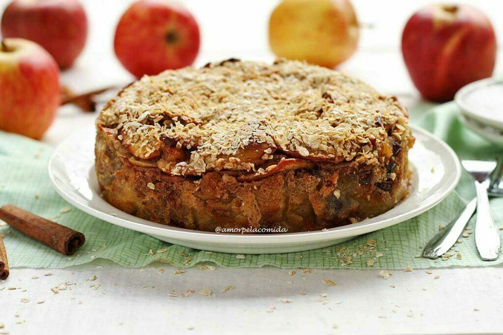 Torta de maçã redonda com cobertura de flocos de aveia sobre prato branco, ao fundo algumas maçãs desfocadas