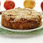 Torta de maçã redonda com cobertura de flocos finos de aveia sobre mesa branca com maçãs ao fundo