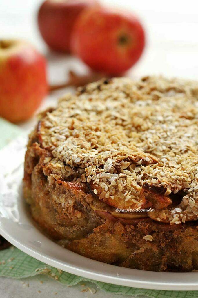 Torta de maçã rústica sobre prato branco, no topo da torta flocos de aveia, ao fundo maçãs desfocadas