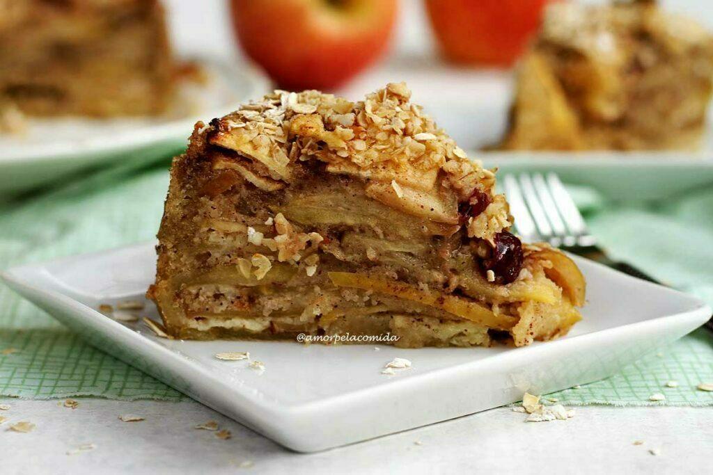 Fatia de torta de maçã sobre prato branco pequeno mostrando todas as camadas de maçã e algumas passas, no topo flocos de aveia