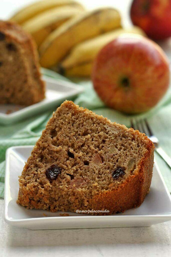 Fatia de bolo de banana e maçã com uva passa na massa sobre prato branco quadrado pequeno, ao fundo mais uma fatia de bolo e frutas desfocadas