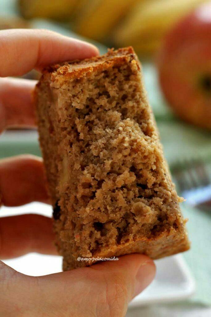 Mão segurando pedaço de bolo mordido mostrando a textura aerada da fatia