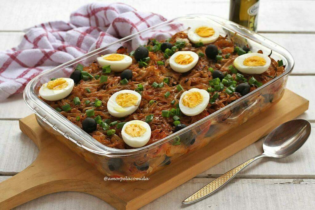 Travessa grande de vidro com bacalhoada dentro, coberta com ovos cozidos e azeitonas pretas