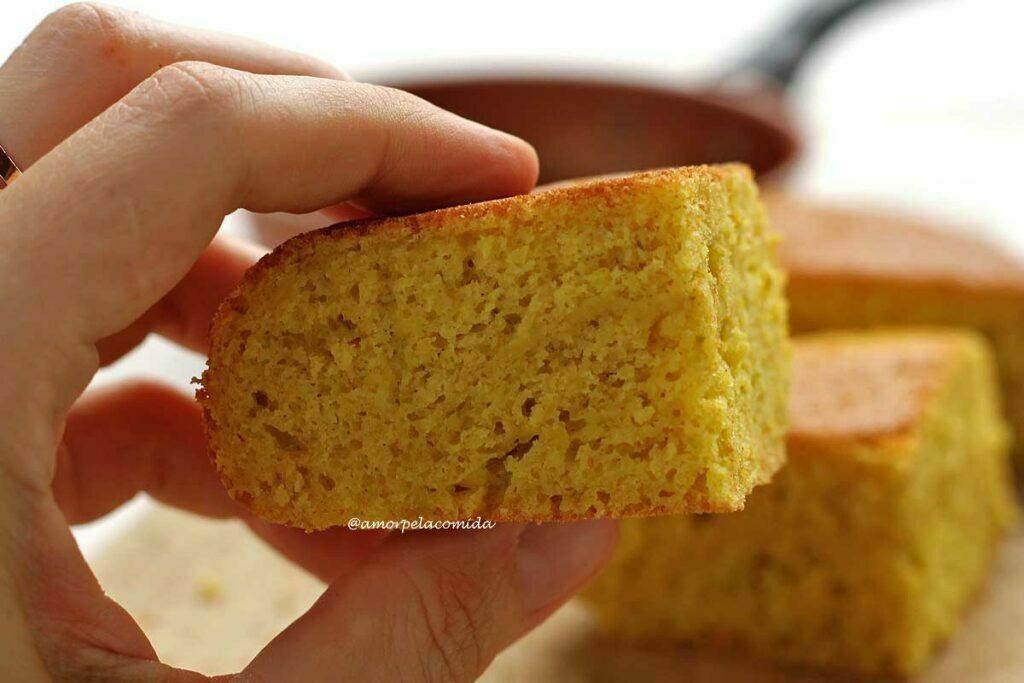 Mão segurando pedaço de bolo de laranja para mostrar a textura interna do pedaço que é aerada