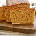 Pão com três fatias cortadas apoiadas sobre o pão de mandioca em uma tábua de madeira