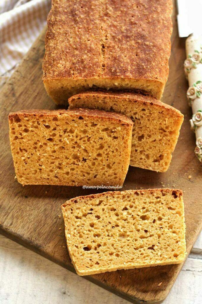 Três fatias de pão de mandioca espalhadas na tábua de madeira próximo ao pão que ainda não foi fatiado