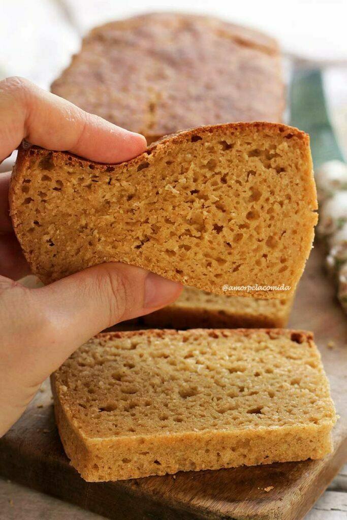 Pão pressionando 1 fatia de pão de mandioca para mostrar a flexibilidade do pão