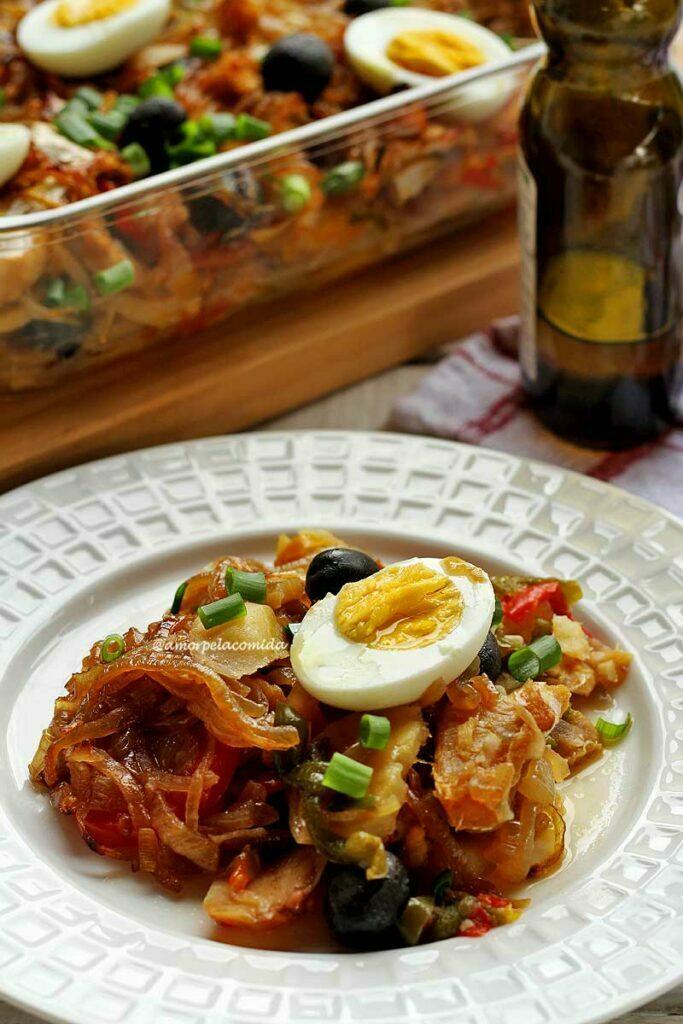Prato branco redondo com bacalhoada dentro, diversos vegetais e por cima metade de um ovo cozido