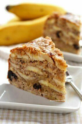 Fatia de torta de banana sobre prato quadrado branco pequeno, ao fundo mais um pedaço triangular e bananas desfocadas