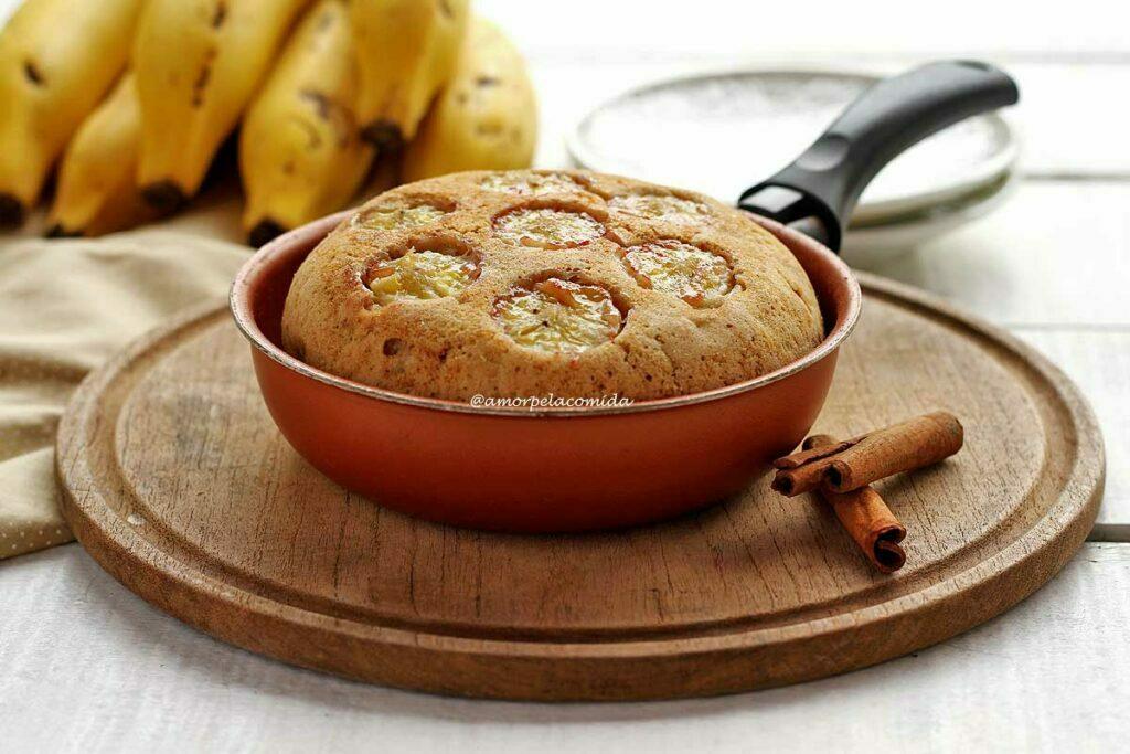 Frigideira marrom com cabo preto sobre tábua de madeira redonda, dentro da frigideira um bolo de banana com rodelas de banana no topo